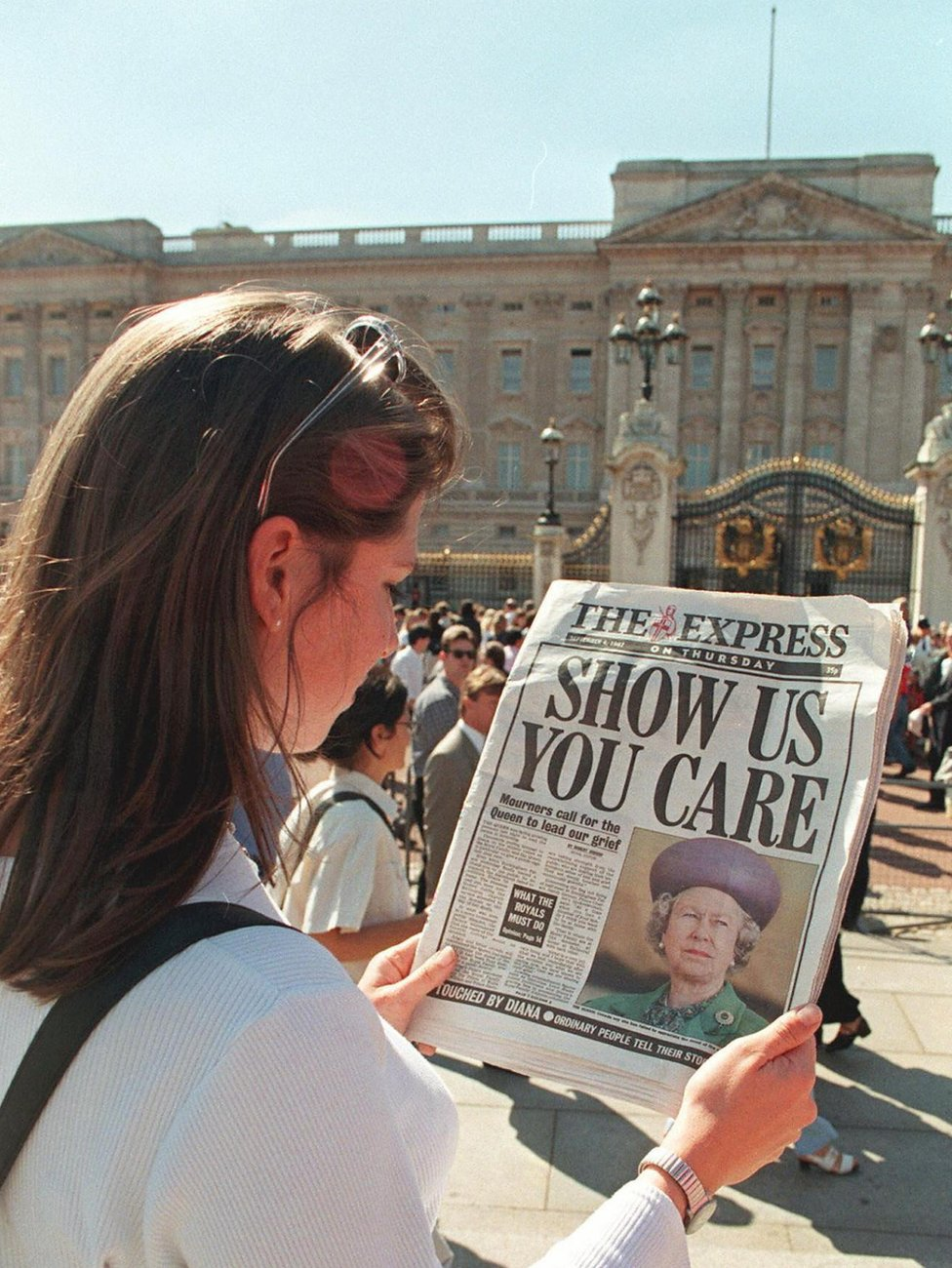 A woman reads a newspaper headline from 4 September 1997, criticising the Queen's silence since the death of Diana, Princess of Wales, the previous weekend