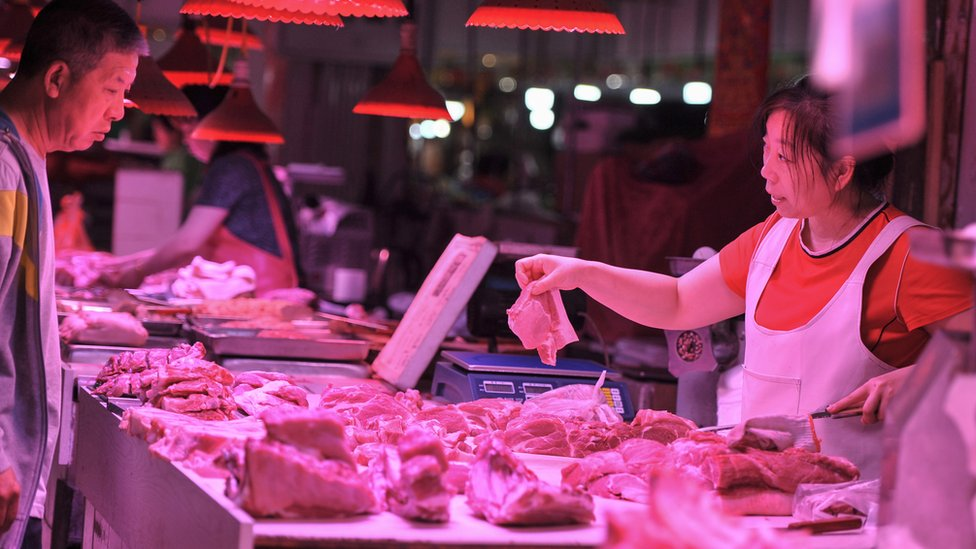 A customer (L) buys meat at a market in Shenyang in China's northeastern Liaoning province on June 12, 2019.