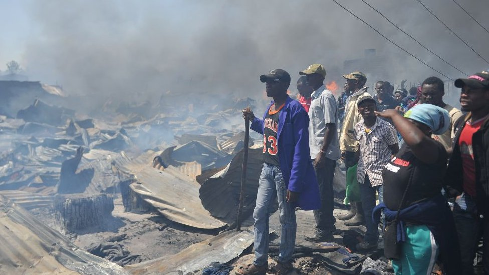 People look at the destruction a fire has done to the stalls