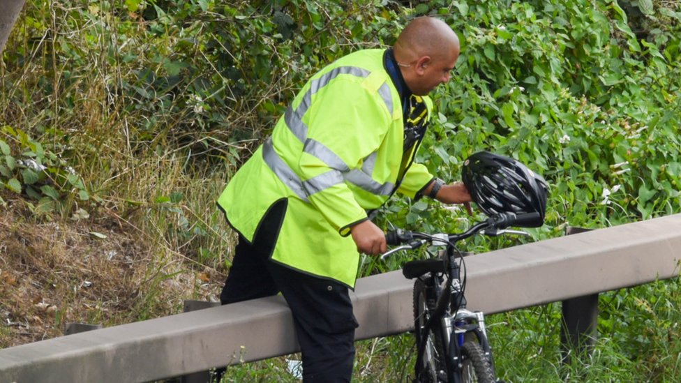 A police officer retrieves a bicycle from the scene
