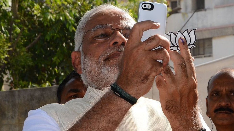 Indian Prime Minister Narendra Modi takes a 'selfie' after casting his vote at a polling station in Ahmedabad