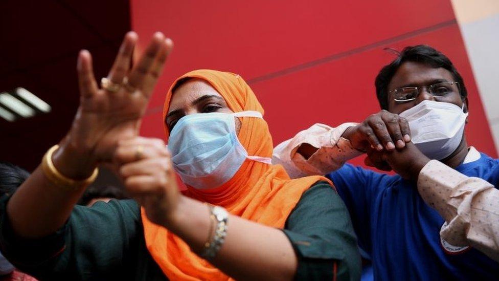 Petugas kesehatan di India menunjukkan pada masyarakat cara mencuci tangan dengan benar menggunakan cairan pembersih.