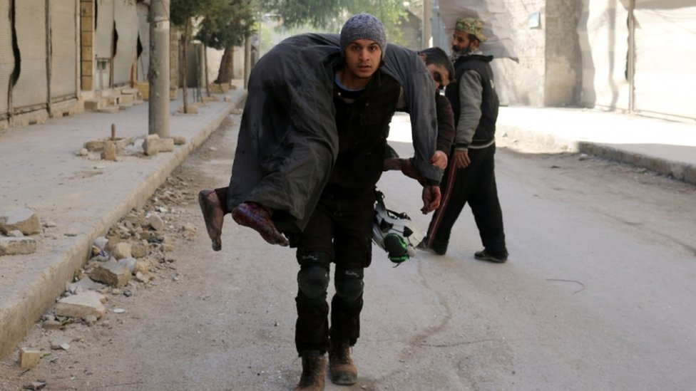 A Syrian civil defence volunteer carries an injured man, 19 November
