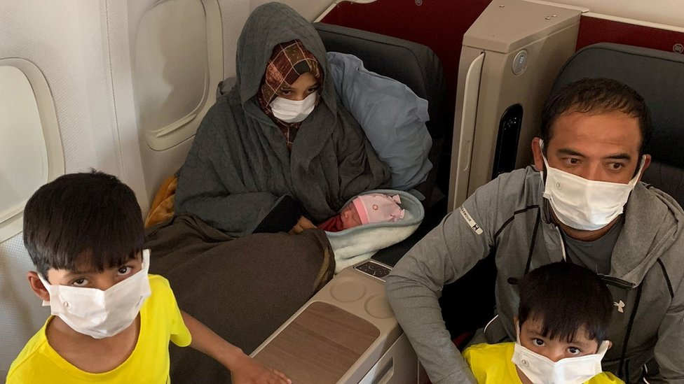 """Afghan evacuee Soman Noori, accompanied by her husband Taj Moh Hammat and their sons, holds her newborn baby girl named Havva on board an evacuation flight operated by Turkish Airlines from Dubai to Britain""""s Birmingham, August 28, 2021"""