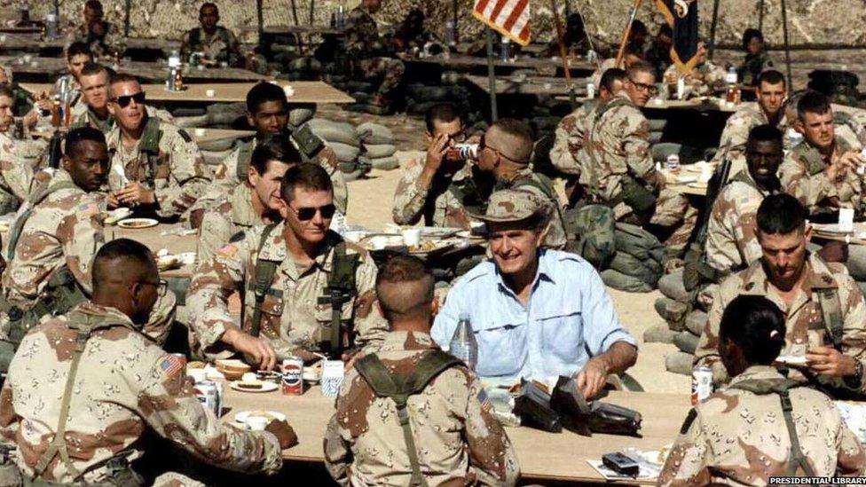 George HW Bush celebrating Thanksgiving with the troops in Saudi Arabia during Desert Shield, November 22, 1990