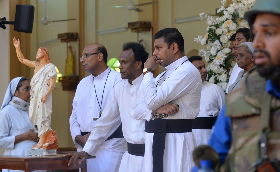 Catholic priests stand inside the church after a bomb blast in Negombo