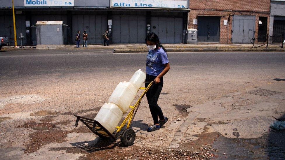 Una mujer traslada bidones de agua en Venezuela