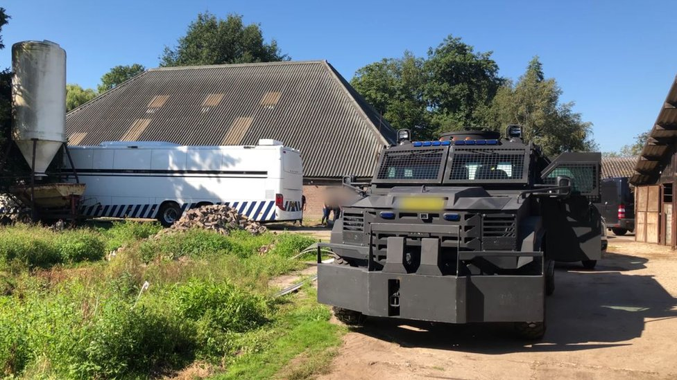Stables with an armoured vehicle in front