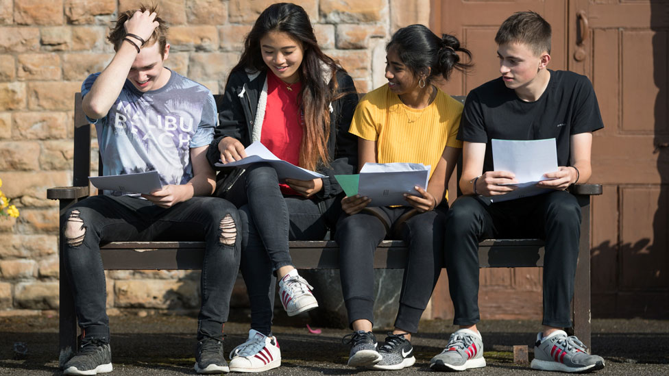 Four students sitting on a bench