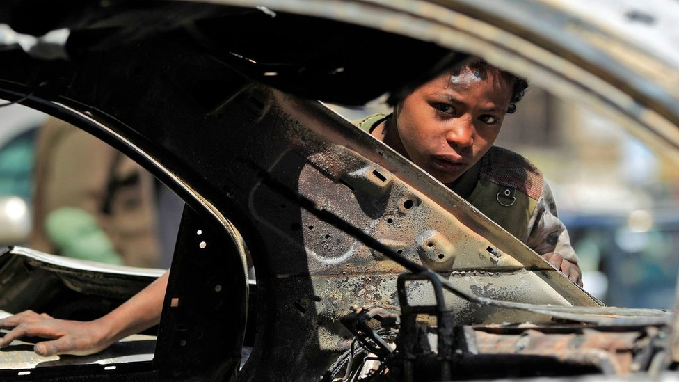 A boy peers through a burnt-out car in Sanaa, Yemen (6 December 2017)