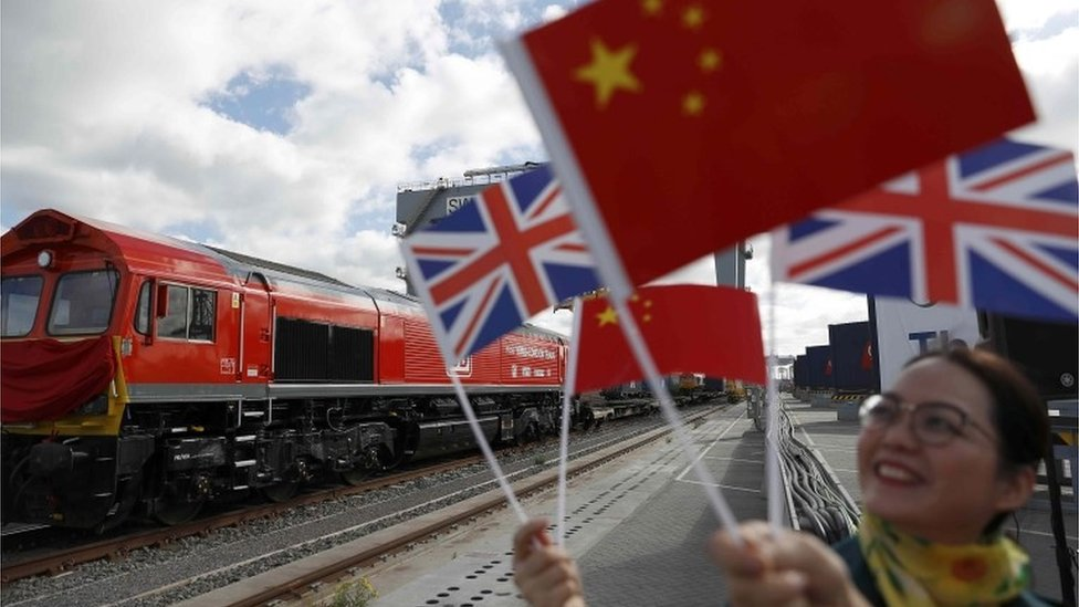 Chinese women wave flages at the official ceremony to mark the departure of the first UK to China export train, laden with containers of British goods, from the DP World London Gateway, Stanford-le-Hope, Britain April 10, 2017.