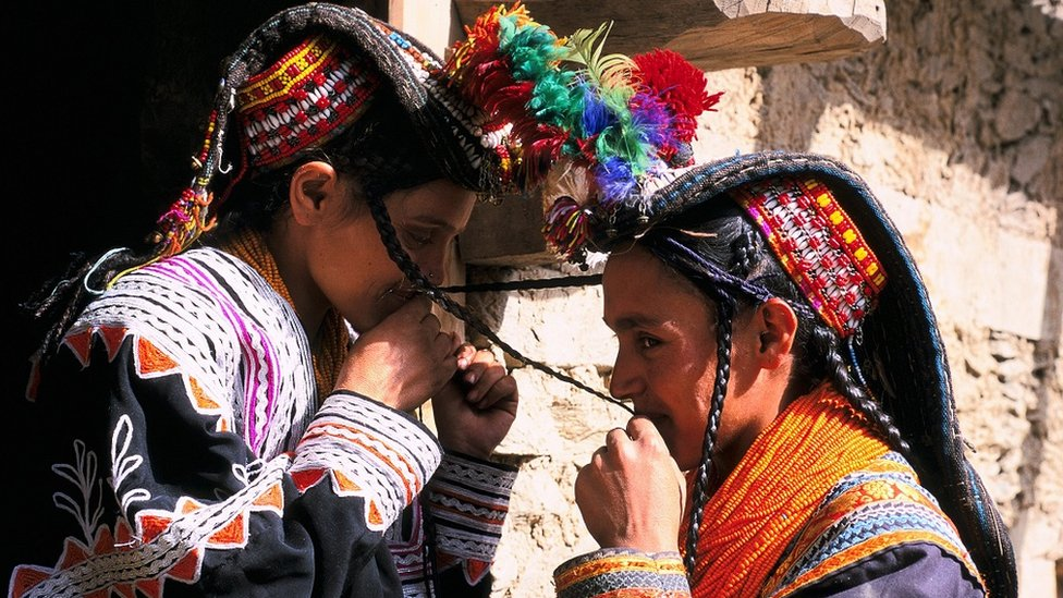 Kalash young girls, dressed in traditional attire, kiss each other's plats, as per tradition
