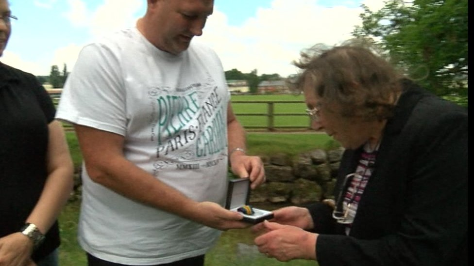 Chris Jeffreys presents the war medal he found to the recipient's daughter-in-law Moira Boaden