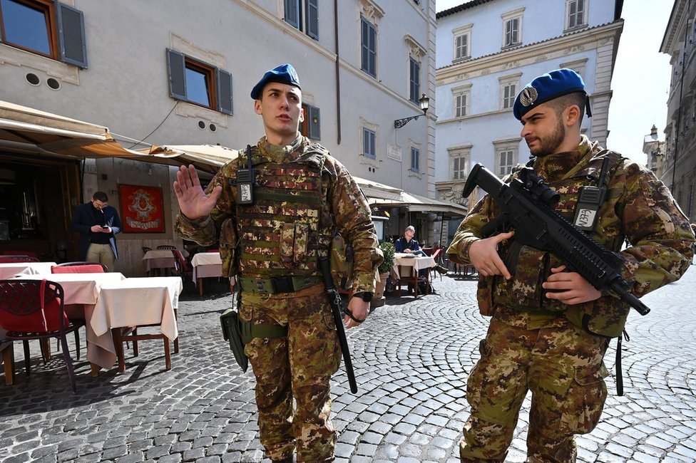 Soldiers with guns walk through a street in Rome
