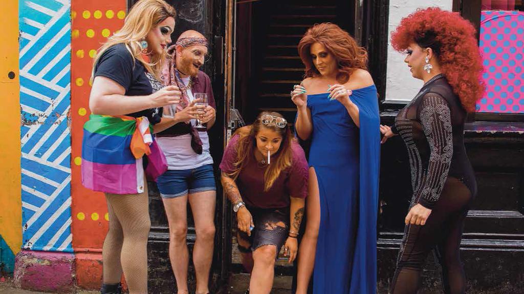 Five people drink outside a bar in Belfast.