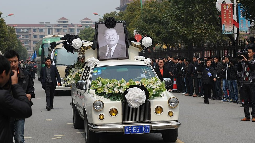 """To go with """"CHINA-SOCIAL-ECONOMY-POLITICS"""" story by Bill Savadove The coffin with the body of retired Communist Party chief, Wu Renbao, is driven through the streets of the village of Huaxi on March 22, 2013."""