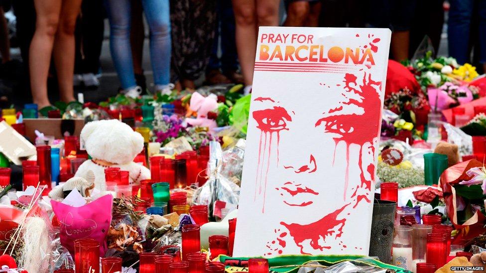 Velas y una pintura de una joven llorando tras el atentado del
