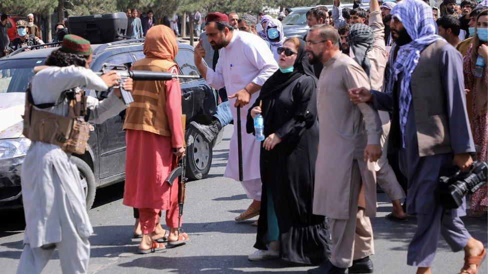 مقاتل لطالبان يواجه متظاهرين.