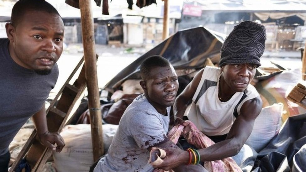 A wounded man reacts at the sight of soldiers while taking shelter in a stall at a market in Harare, on August 1, 2018