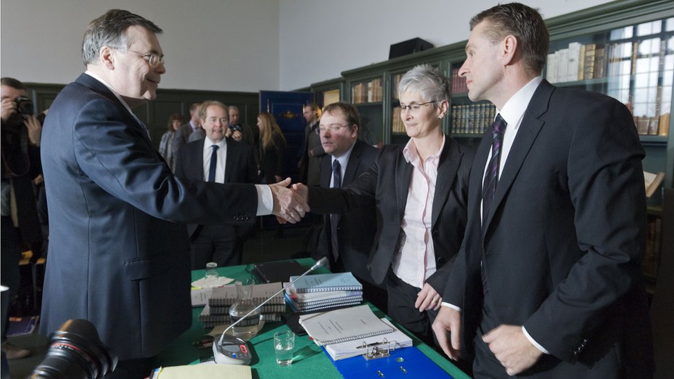 Iceland's ex-prime minister Geir Haarde shakes hands with Parliament prosecutor Sigridur Fridjonsdottir on March 5, 2012.