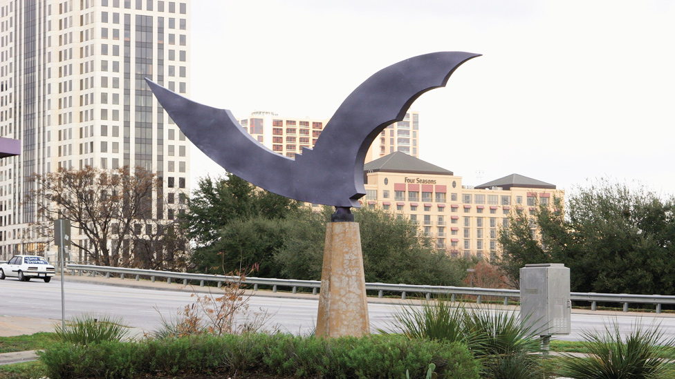 Escultura del artista Dale Whistler de un murciélago en metal en una calle en Austin