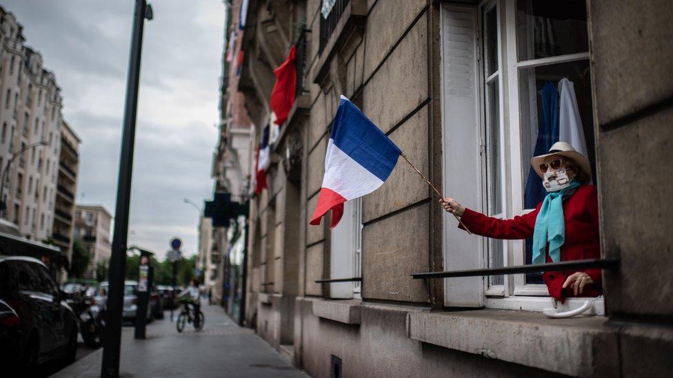 Mujer con una bandera de Francia y mascarilla en un balcón de París