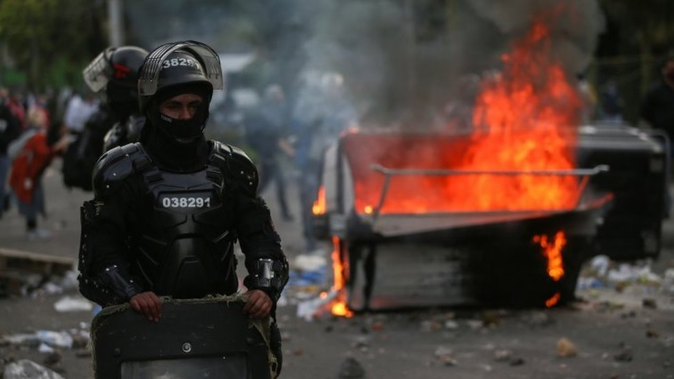 Riot police stand next to a burning garbage container during clashes with protesters after a man, who was detained for violating social distancing rules, died from being repeatedly shocked with a stun gun by officers, according to authorities, in Bogota, Colombia September 9, 2020.