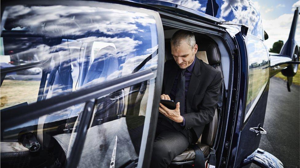 Un hombre observa su tableta dentro de un helicóptero