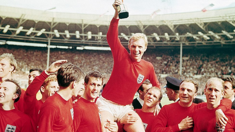 "England captain Bobby Moore ""chaired"" by his team with the Jules Rimet Cup...after receiving it from the Queen after England won the Cup final 4 goals to 2, against West Germany."