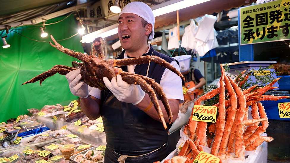 A vendor holds up a crab at the Tsukiji market