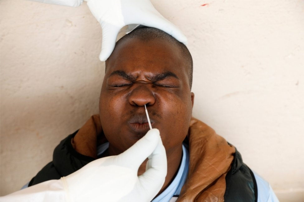 A man clamps his eyes and mouth shut as a swab is inserted into his nose.