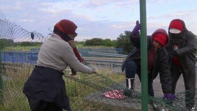 Three migrants near Eurotunnel terminal in Calais climbing over a broken fence