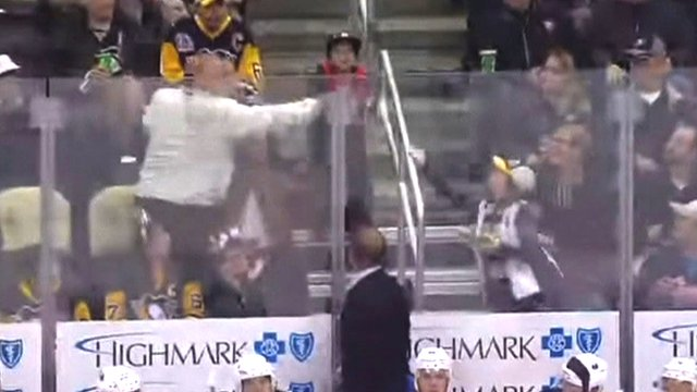 A man catches a puck intended for a young Pittsburgh Penguins ice hockey fan