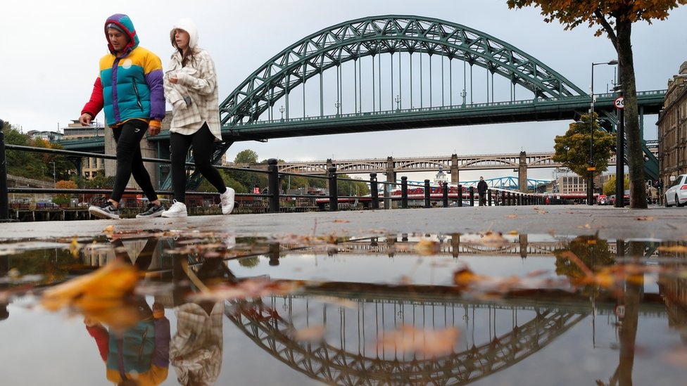 A couple walk along Newcastle's Quayside with the Tyne Bridge in the background
