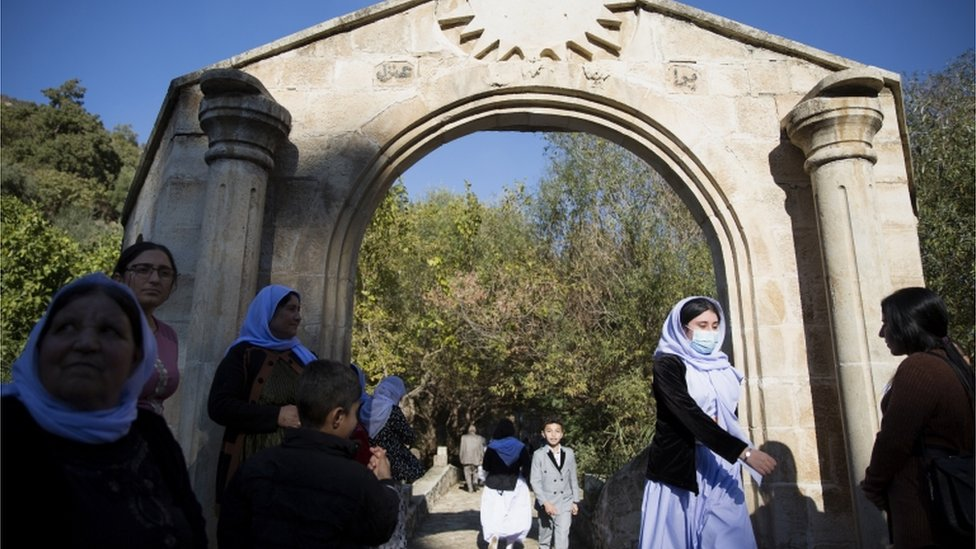 People walk through an arch in Lalish, the Yazidis' holiest site