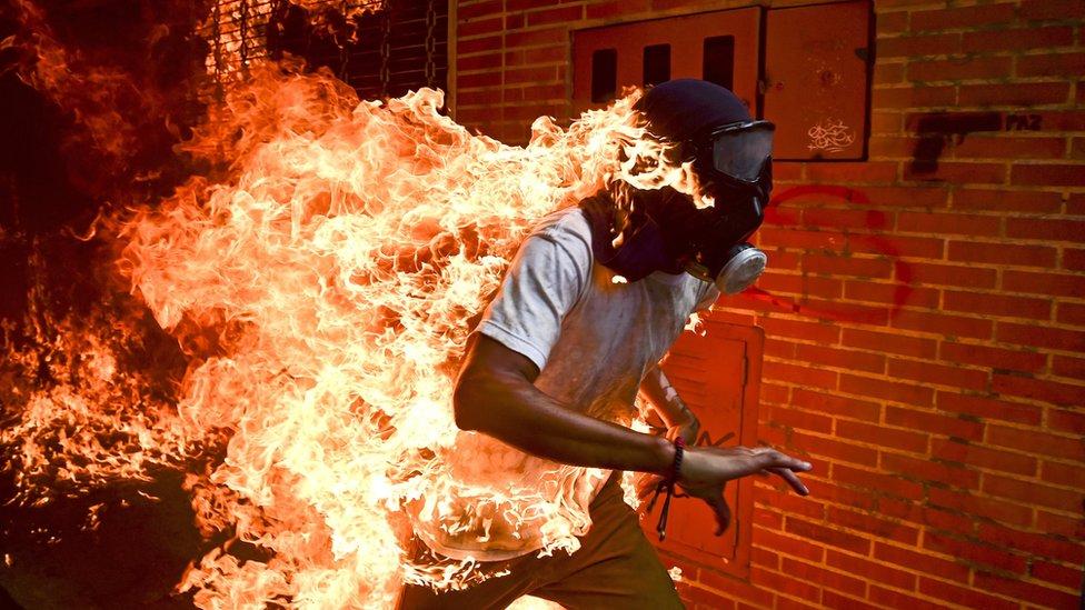 En la imagen el joven de 28 años José Víctor Salazar corre prendido en llamas en medio de una protesta antigubernamental en Caracas.