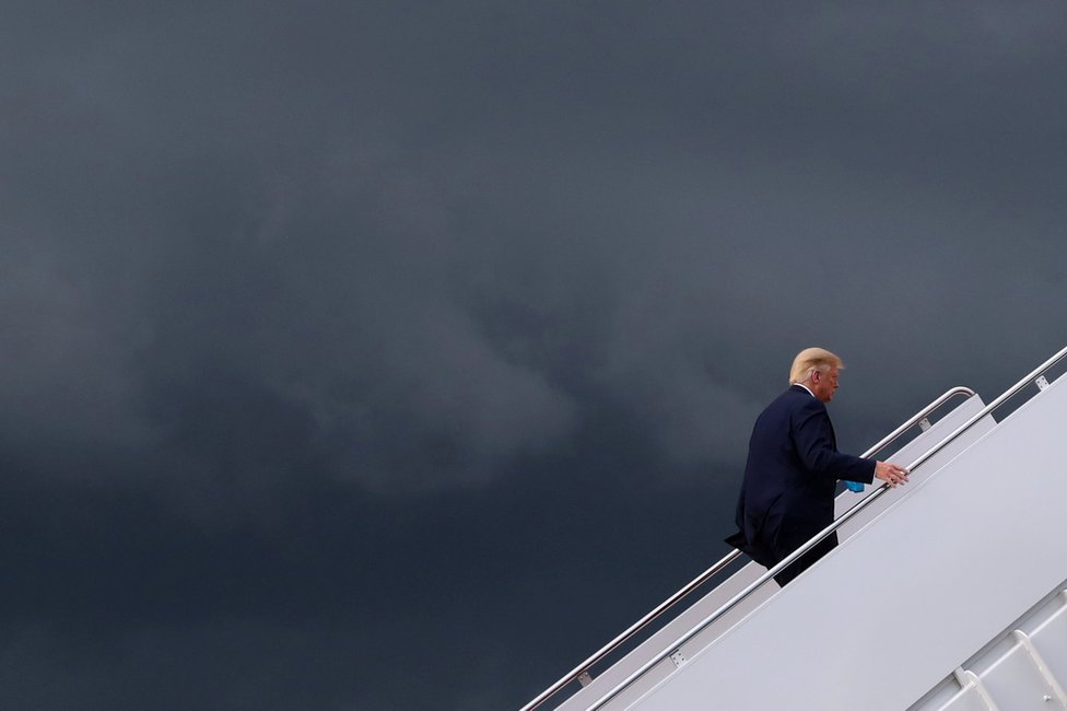 President Donald Trump climbs the stairs to board Air Force One