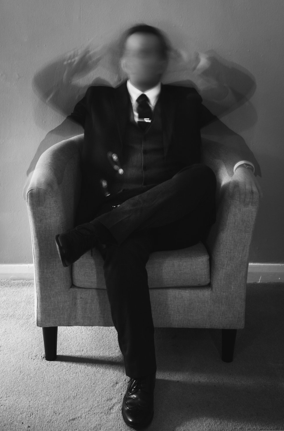 A blurred photo of a man sitting in a chair waving his arms around