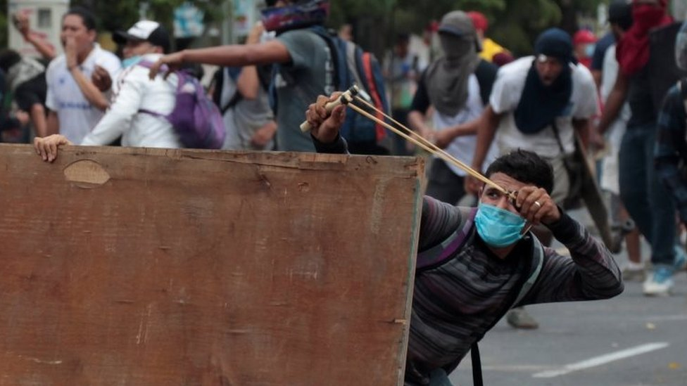 A demonstrator uses a slingshot to hurl stones toward riot police during a protest over the pension plans of the Nicaraguan Social Security Institute (INSS) in Managua, Nicaragua April 20, 2018