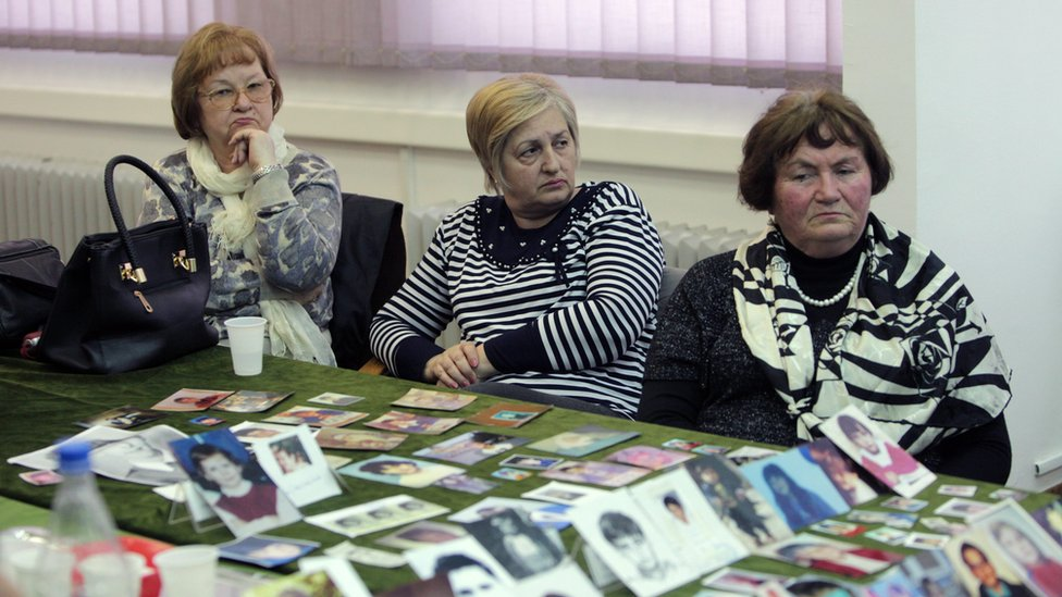 Sarajevo women watch the reading of the verdict as victims' pictures are displayed on a table - 24 March