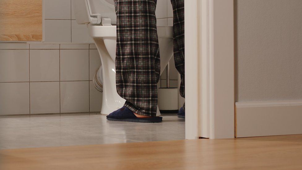 Un hombre parado frente al inodoro.