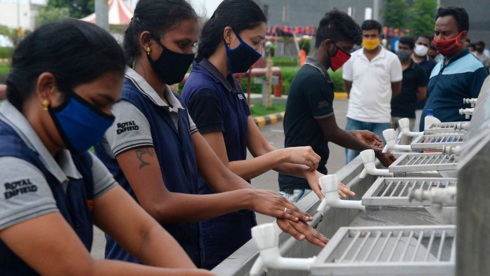 Workers washing their hands upon their arrival at the Royal Enfield motorcycle factory after the government eased a nationwide lockdown imposed as a preventive measure against the COVID-19 coronavirus, in Oragadam, Tami Nadu.