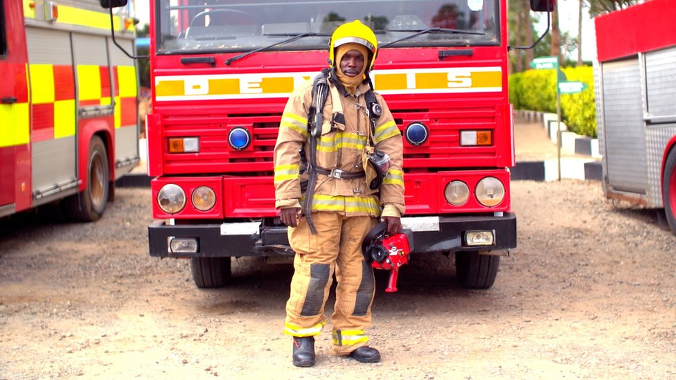 Kenyan firefighter in front of fire engine