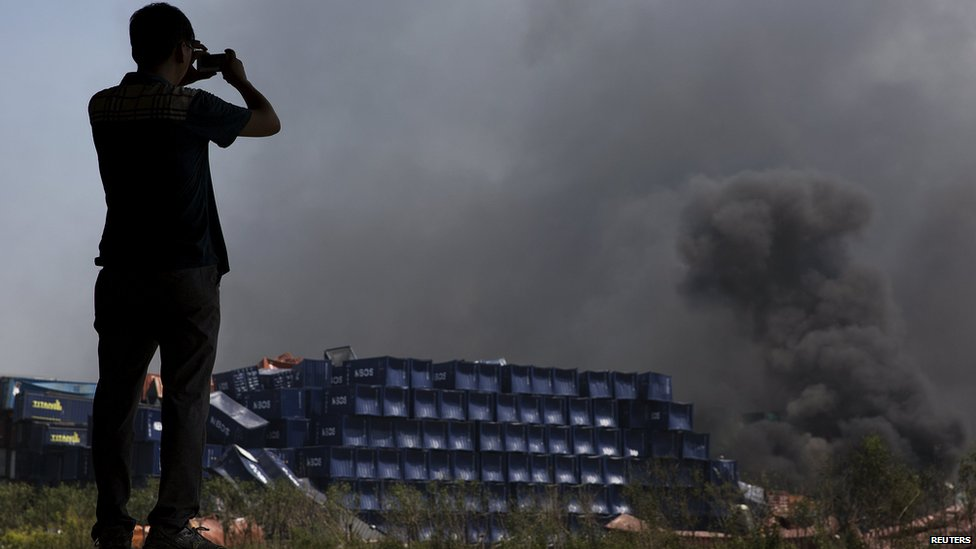 A man takes pictures at the explosion site in Binhai new district in Tianjin, China August 13, 2015.