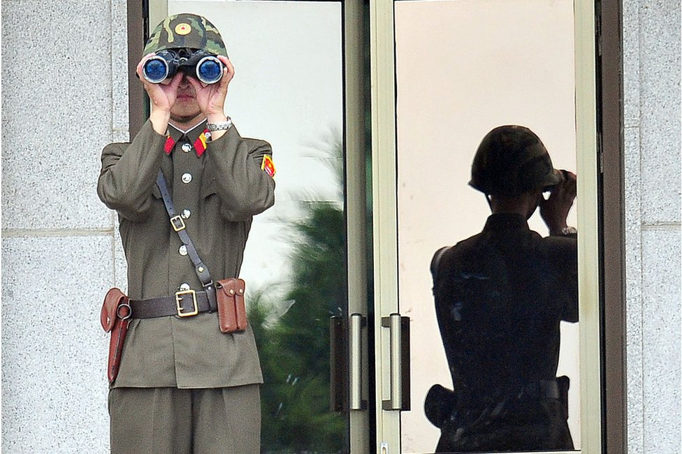 A North Korean soldier looks at the South side as government delegations from the UN allied nations visit the truce village of Panmunjom in the Demilitarized zone (DMZ) dividing the two Koreas on 27 July 2013 to mark the 60th anniversary of ceasefire agreement and UN forces' participation in the Korean War.