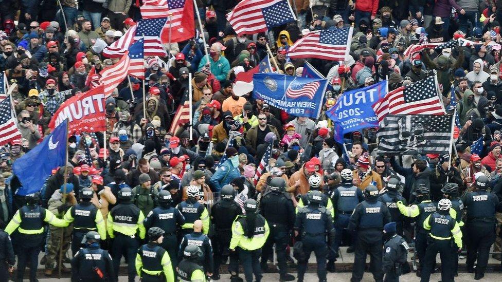Una muchedumbre de seguidores de Trump se acerca a la barrera de seguridad policial del Capitolio