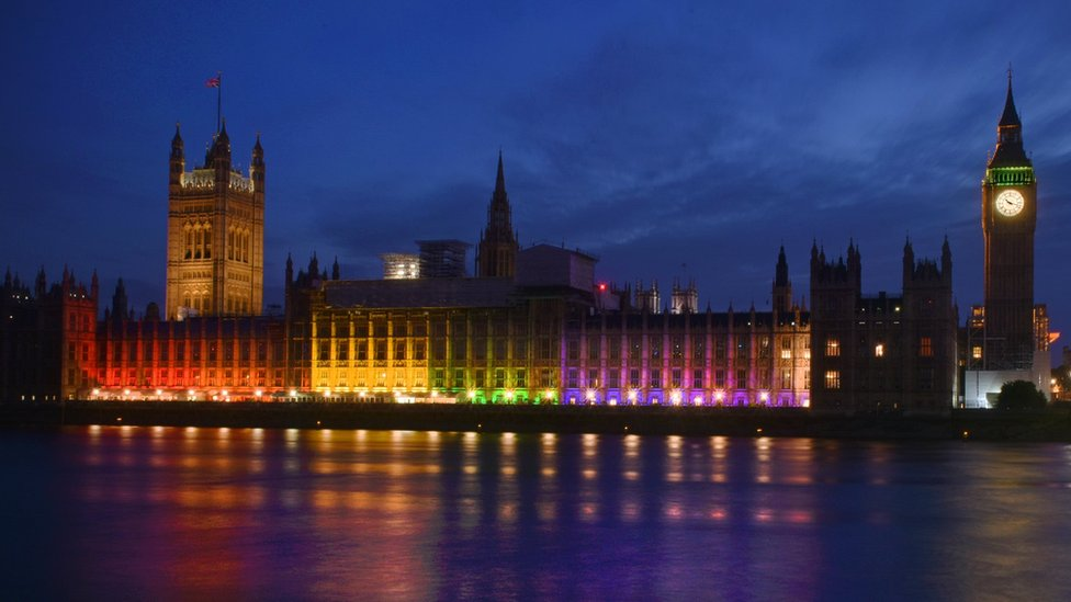 Houses of Parliament lit up with the rainbow flag