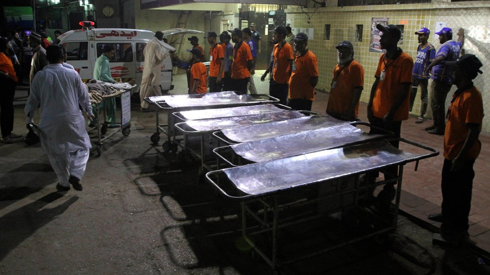 Staff members of a local hospital wait for casualties of bomb blast at a Sufi shrine, in Karachi, Pakistan
