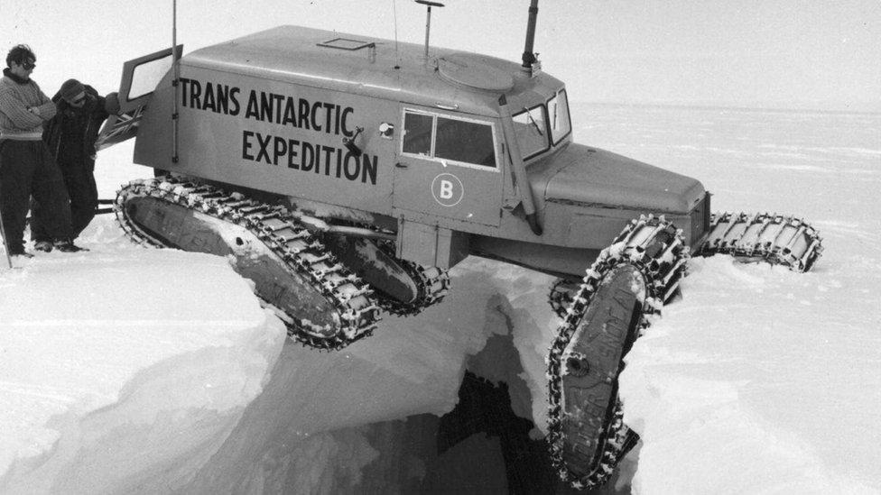 Vehículo con orugas balanceándose sobre una grieta en el hielo