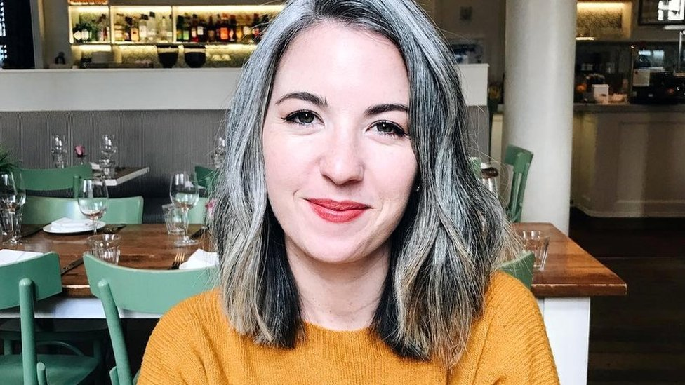 Kate, who has a grey curly bob, is pictured sitting in a restaurant